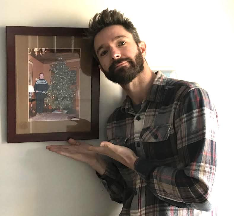 A man stands next to a framed Christmas photo.