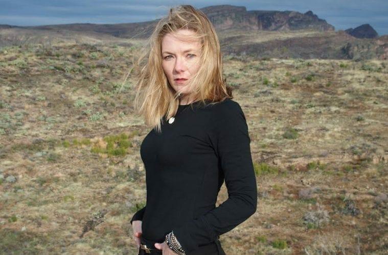 Poet Julie Bloemeke stands outdoors.