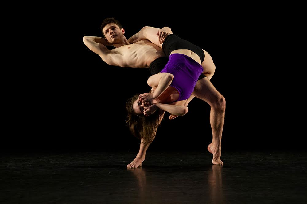 Two Kennesaw State University dance students perform on a darkened stage.