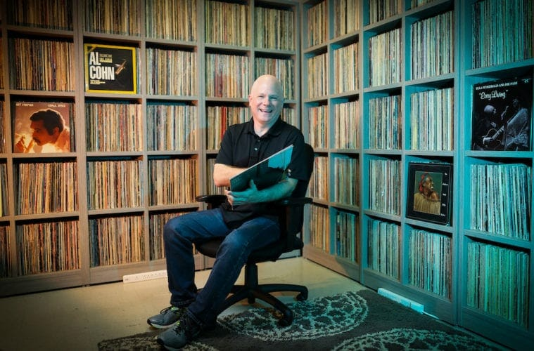 Sam Skelton sits in front of 9,000 vinyls records donated to Kennesaw State University.