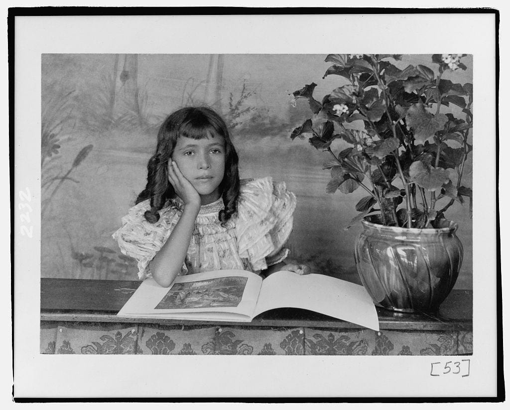 """Thomas Askew: """"Daughter of Thomas E. Askew, head-and-shoulders portrait, seated, right hand on cheek, with open book"""" (est. date 1899 or 1900). Silver gelatin. Image courtesy Library of Congress."""