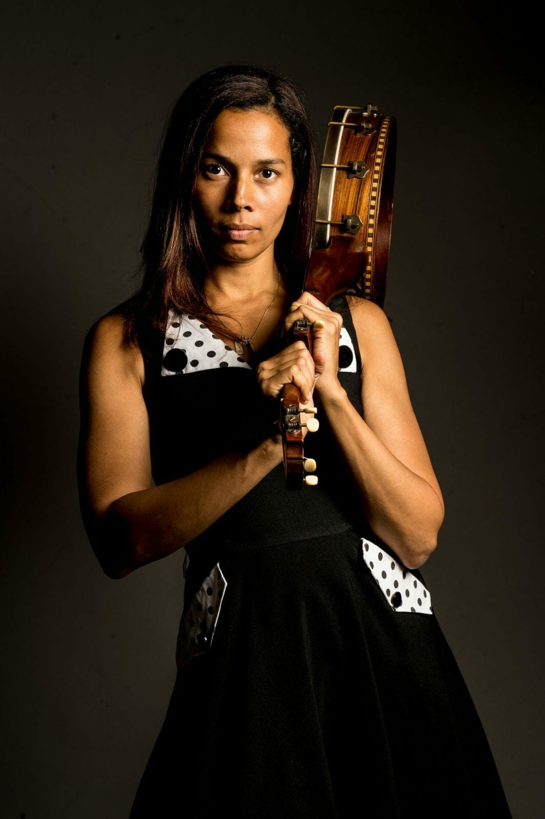 Rhiannon Giddens holds her banjo over her shoulder.