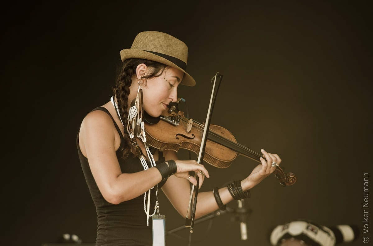Rising Appalachia's Chloe Smith plays the fiddle on stage.