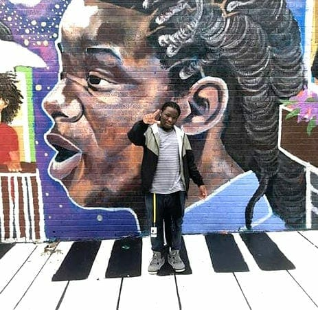 "sedtheprodigy in front of his image on the ""Flight of the Fireflies"" mural."