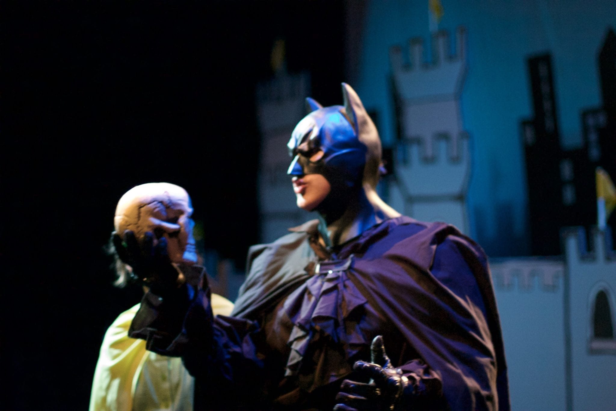 Batman holds a skull in the style of Shakespeare's Hamlet