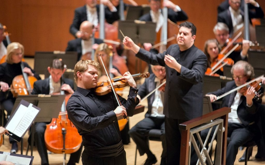 David Coucheron, center, with guest conductor Munoz. (Photo by Jeff Roffman)