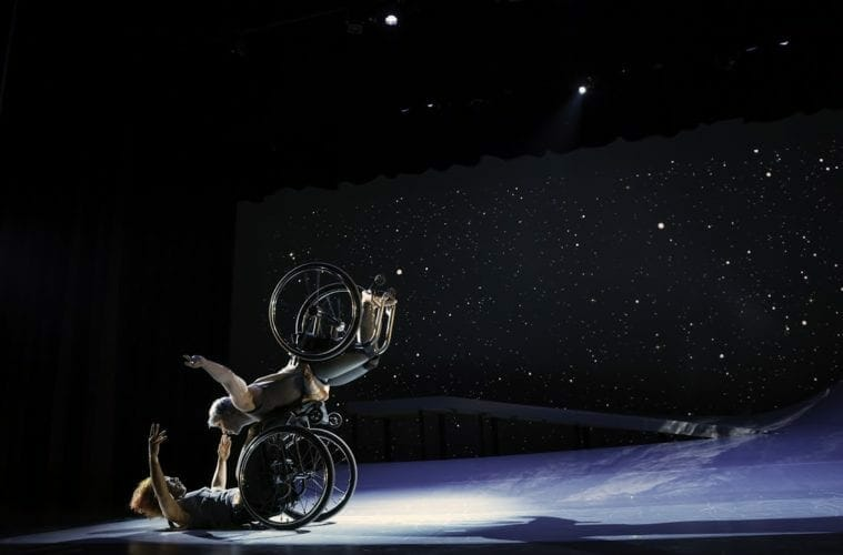Two disabled dance artists from Kinetic Light perform on stage.