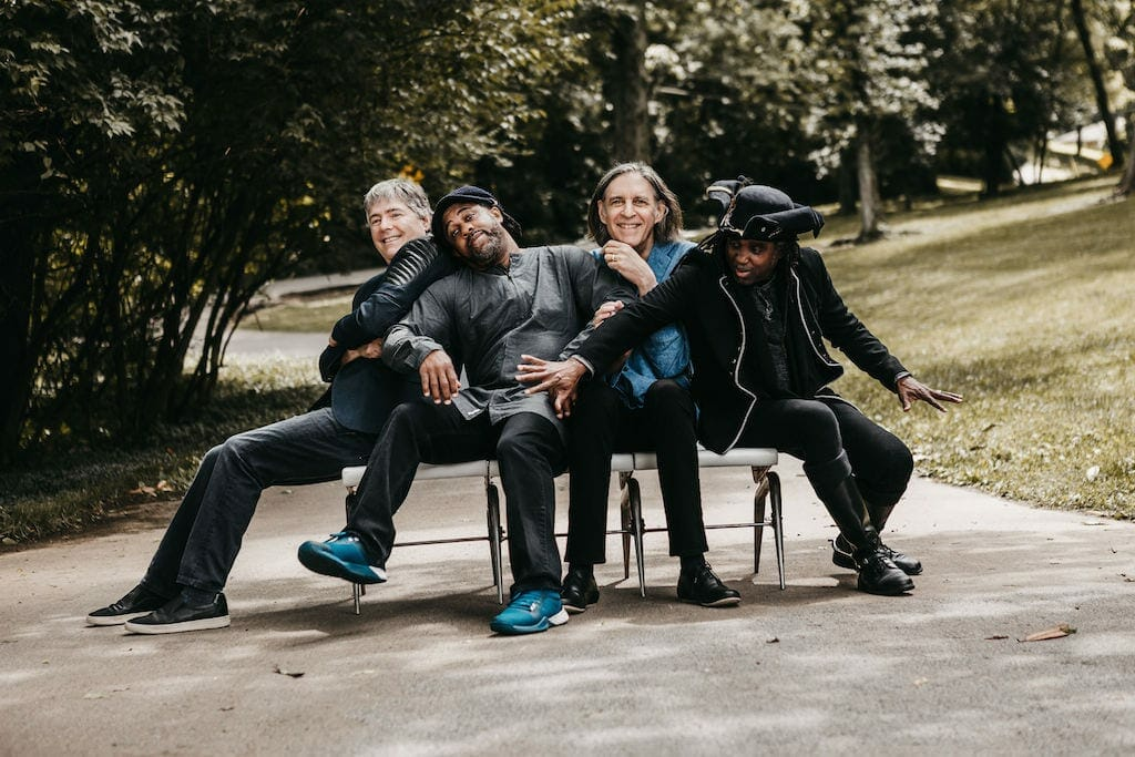 Bela Fleck and the Flecktones pose outdoors.