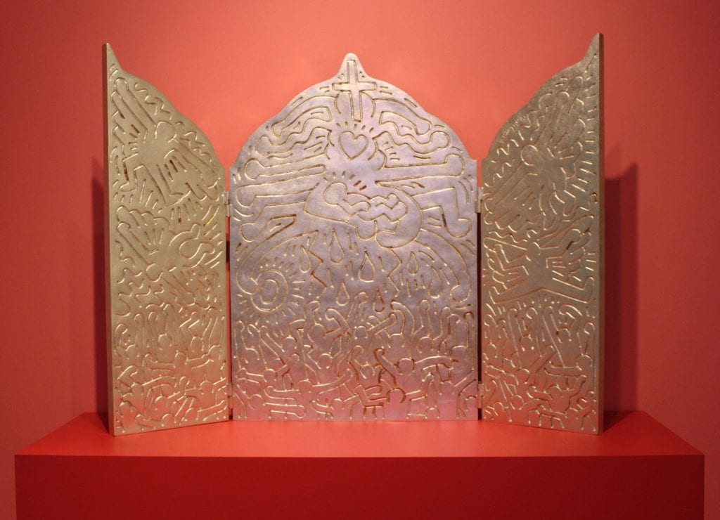 Installation shot of Keith Haring, Altar Piece, 1990, cast 1996. Bronze with white gold-leaf patina, edition 2 of 9, 60 x 81 x 2 inches. Denver Art Museum, Gift of Yoko Ono, 1996. 204 A-C.