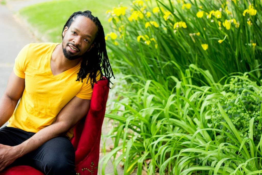 Poet Jericho Brown in a field.