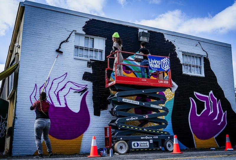 Paris street artist Kashink paints her mural on a wall outside Twain's Brewpub & Billiards in Decatur.
