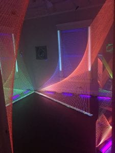 """Vivid Imaging (The Poetics of Space)"" 2016. installation; size variable; twine hand-painted with invisible UV, eyelets, wood, and blacklight at Kibbee Gallery. Photo courtesy Megan Mosholder."