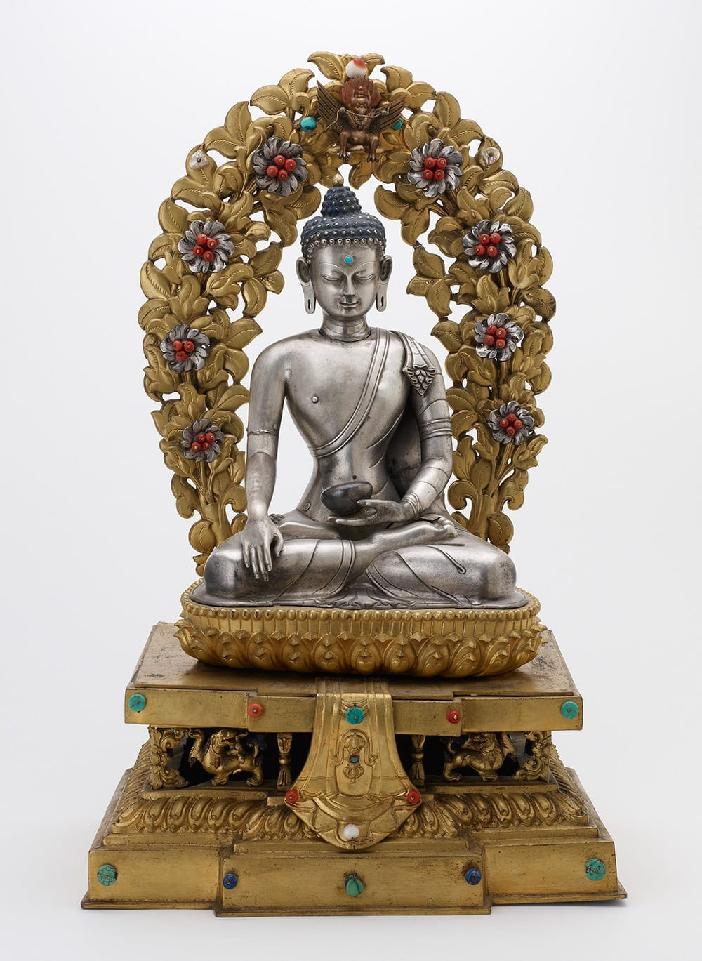 Shakyamuni Buddha in a Full Shrine  Qing; probably Dolonnor Second half of the 18th to early 19th century Silver repoussé image with turquoise urna; flora mandorla with leaves of gilt copper and flowers of silver with coral and mother-of-pearl; a solid cast garuda bird at the peak; heavily gilded bronze lotus seat and base with inset turquoise, coral, and lapis lazuli; base sealed with a copper plate incised with a double vajra; contents inside.  Photo courtesy of The Freer Gallery of Art and Arthur M. Sackler Gallery, Smithsonian Institution. From The Alice S. Kandell Collection.