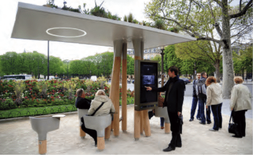 A WIFI hot spot/rest stop/ad wrapper in Paris features a green-roofed platform with  swiveling concrete seats, desks and electrical outlets