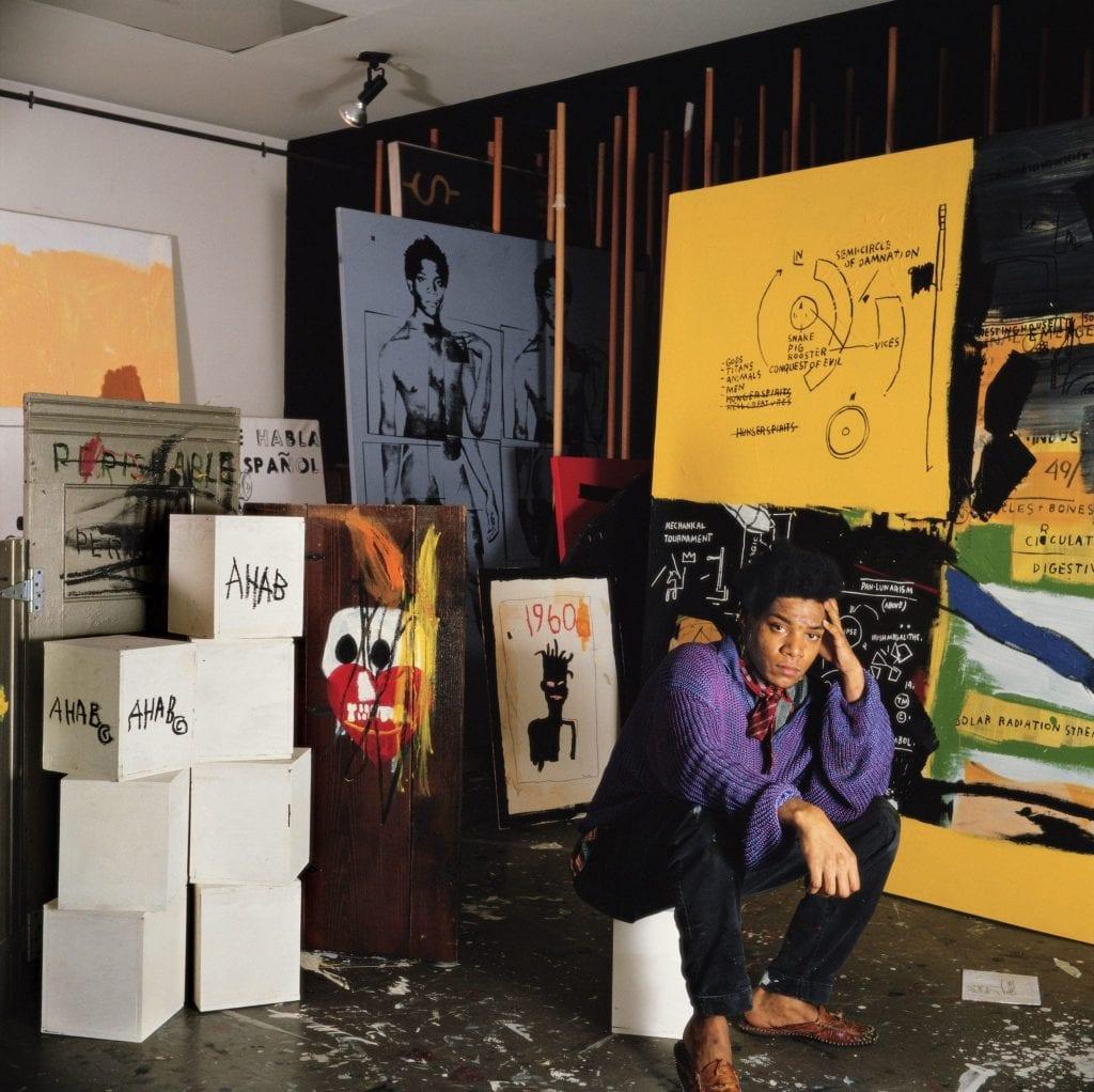 Tseng Kwong Chi (Chinese-Canadian-American, born Hong Kong, 1950–1990). Jean Michel Basquiat in his Great Jones Street studio, New York, 1987. Chromogenic development print, 50 x 50 in. (127 x 127 cm). Muna Tseng Dance Projects, New York & Eric Firestone Gallery, East Hampton, New York. © 1987 Muna Tseng Dance Projects, Inc. New York.
