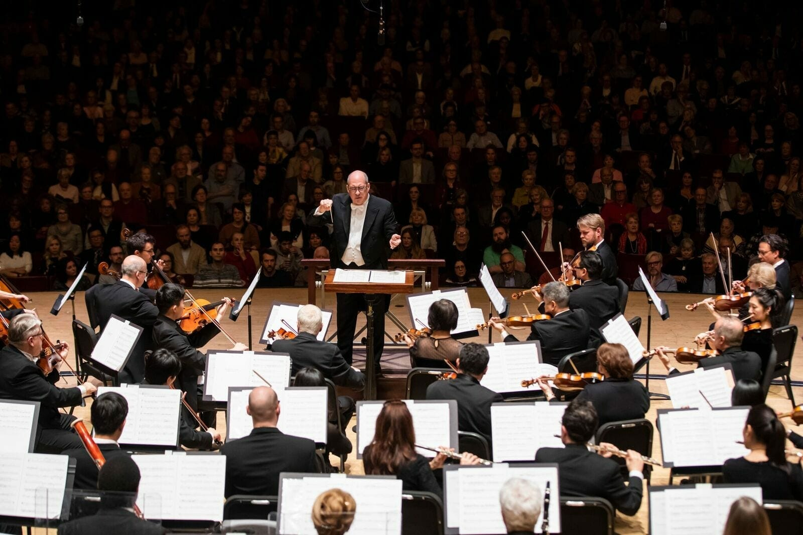 Robert Spano faces the Atlanta Symphony Orchestra as he conducts.