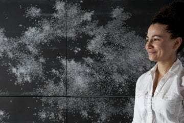 Visual artist Bethany Collins stands in front of one of her works.