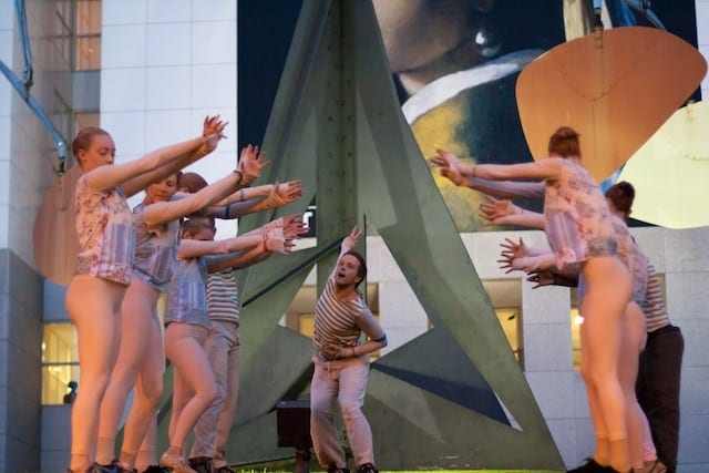 """Sean Hilton passes through two lines of dancers in front of Alexander Calder's kinetic sculpture """"Three Up, Three Down"""" on the Woodruff Arts Center campus."""