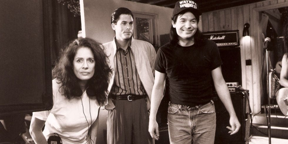 Spheeris on the set of Wayne's World with Rob Lowe and Mike Myers.