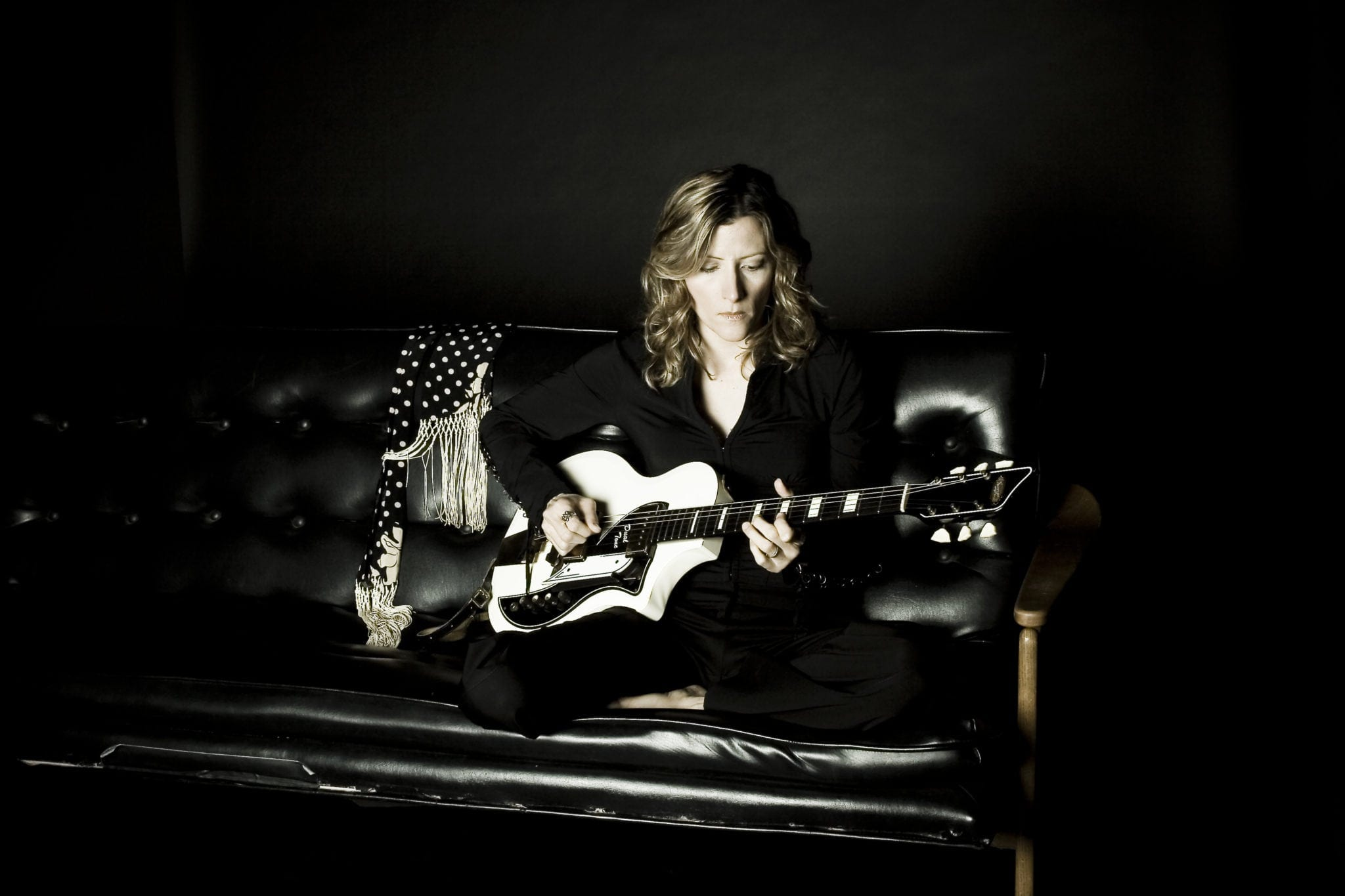 Michelle Malone sitting on a couch playing guitar.
