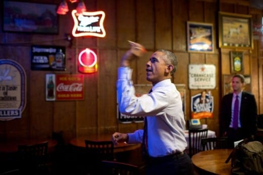 President Barack Obama, one of the many political figures to visit Manuel's, plays darts. (Photo by Hastings Huggins)