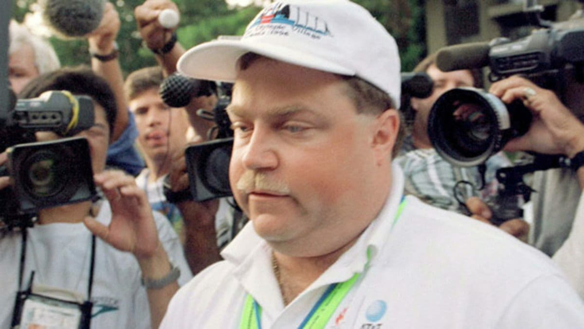 Richard Jewell walks through a crowd of reporters after the 1996 Olympic Games.