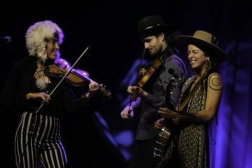 Chloe (left) and Leah Smith of Rising Appalachia perform on stage.