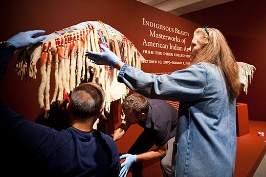 Rebecca Stone, the Carlos Museum's faculty curator of Art of the Americas, directs the installation of a man's shirt from the Apsa'alooke (Crow) of Montana, circa 1874.