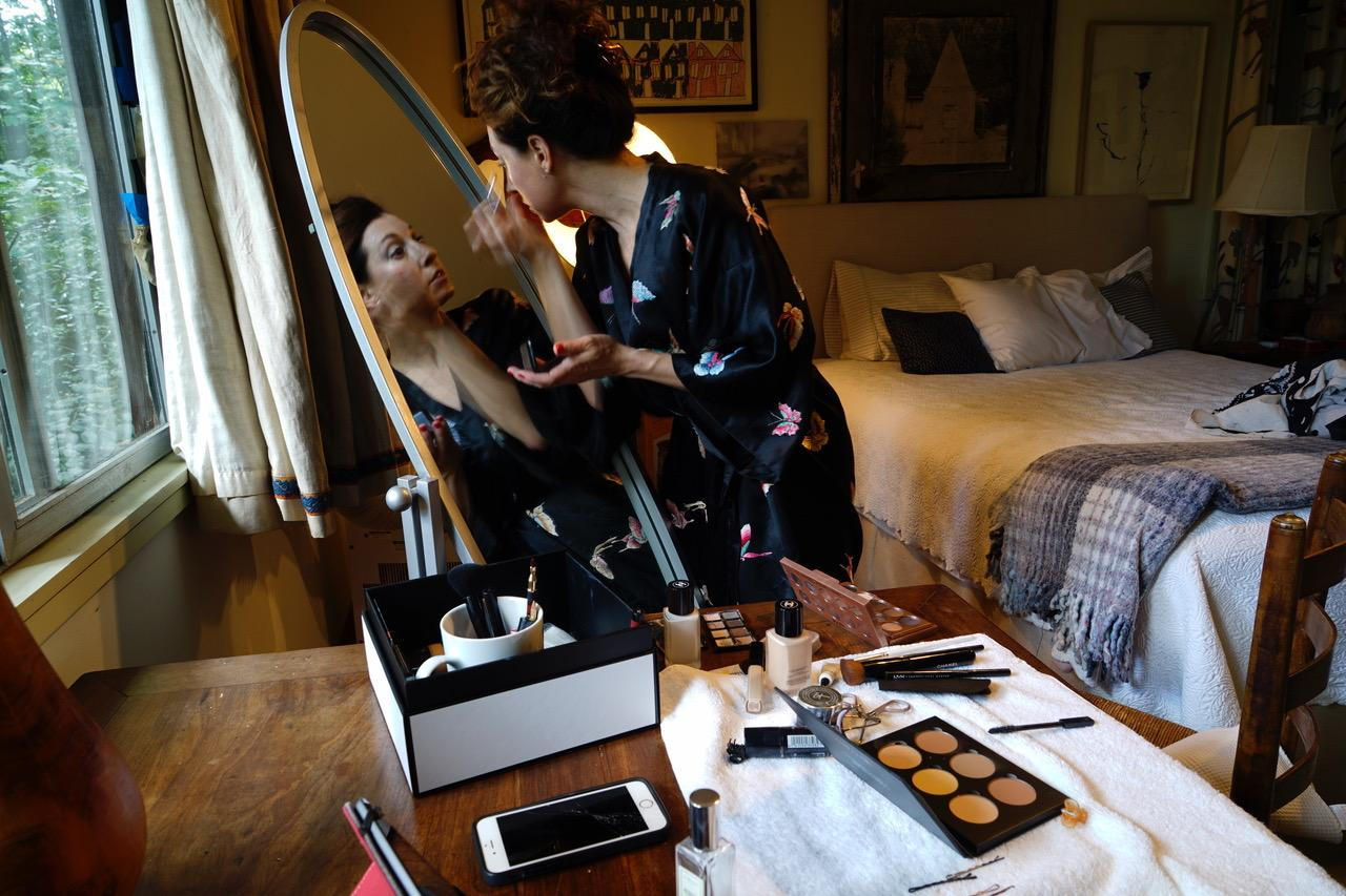 A photo of actress Park Krausen putting on make up in front of a mirror.