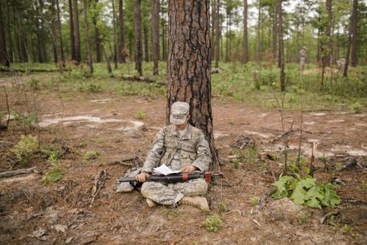 A recruit studies his notes while sitting under a tree in the forest during a multi-day field exercise. From Raymond Jones' Birth of a Soldier.