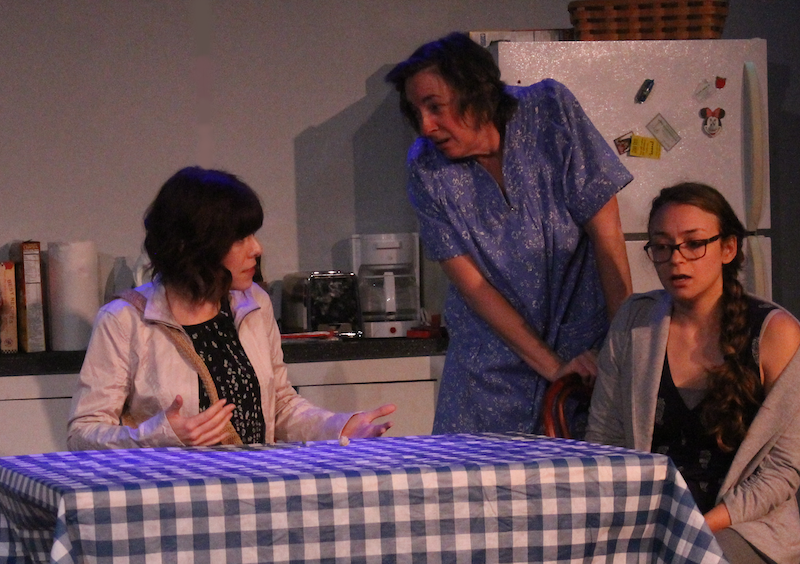 "Three actors perform a scene from ""Built To Float"" around a kitchen table."