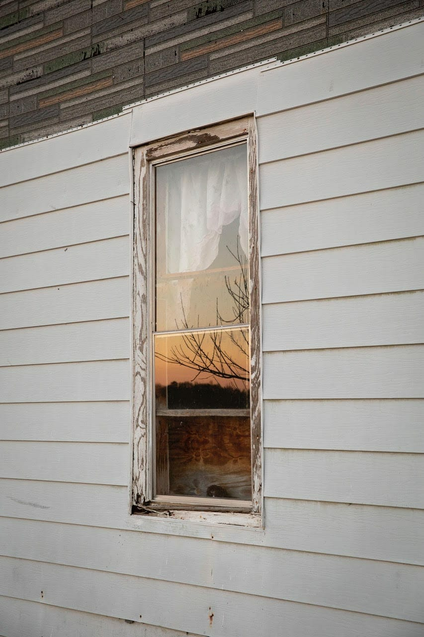 A photo by Amanda Greene of a sunset reflected in the window of an old wood-frame house.