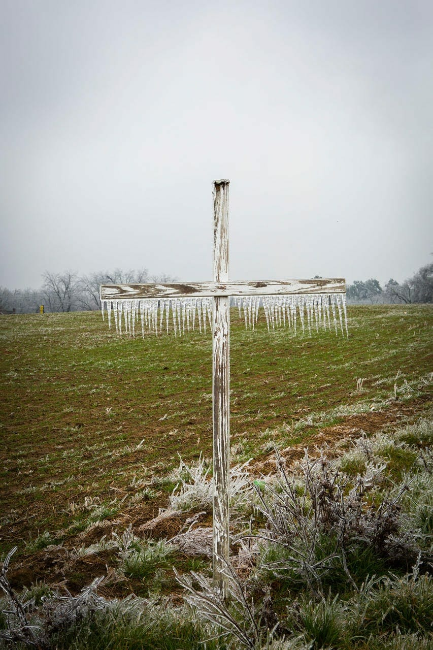 A photo of a wood cross coated in ice in a Georgia field.