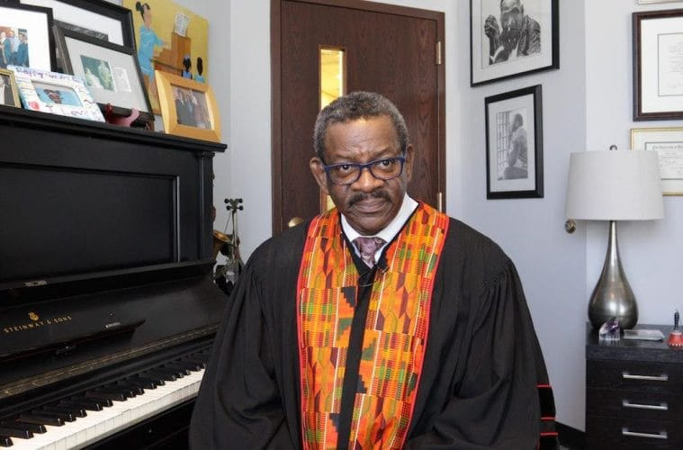 The Rev. Dwight Andrews poses in front of his piano.