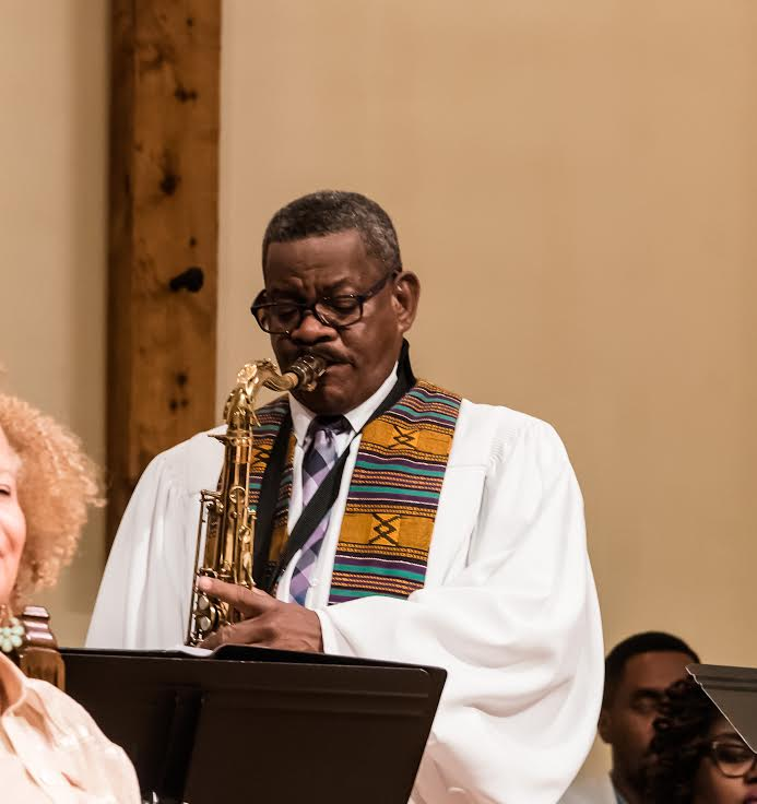 The Rev. Dwight Andrews plays his beloved saxophone during a church service.