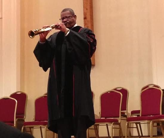 A pastor plays a soprano saxophone during a church service.