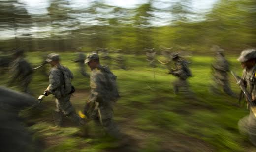 Recruits run through a forest section of Fort Benning during a team combat exercise.